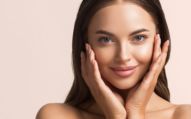 Beautiful woman face close up natural make up hand touching face beauty smile